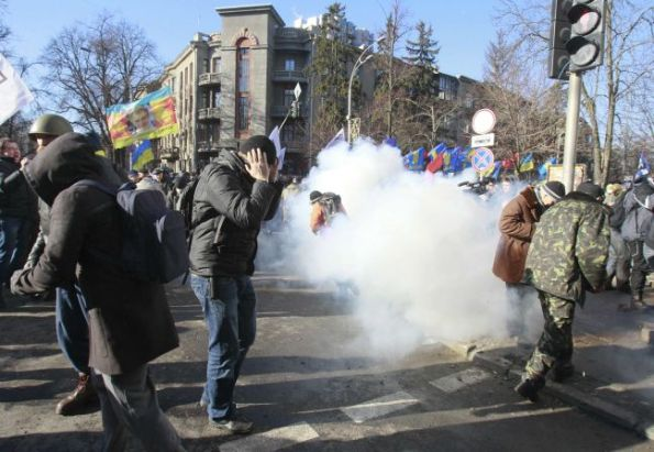 Anti-government protesters react during a rally in Kiev