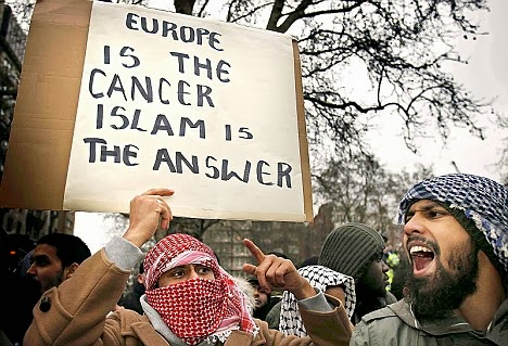 LONDON - FEBRUARY 03:  Muslim demonstrators hold banners at the Danish Embassy on February 3, 2006 in London. British muslims have condemned newspaper cartoons which first appeared in a Danish newspaper, some of which depict the Prophet Mohammed wearing a turban shaped like a bomb. The cartoons have sparked worldwide protests.  (Photo by Peter Macdiarmid/Getty Images)
